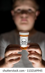 A small child holding a prescription bottle with dangerous medication, illustrating the dangers of prescription drug overdose and drug abuse in children and child and teen suicide.