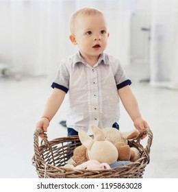 A small child holds a basket with toys. Square. The concept of childhood, education, family.