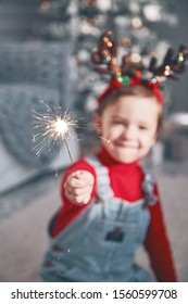 A small child holds a burning sparkler in his hand. Christmas celebration.