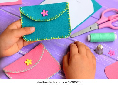Small child holds a felt purse in his hand. Child shows a felt purse. Handcraft supplies on a wooden table. Funny and easy hand sewing project for kids