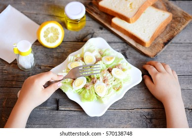 Small child holds a fork in his hand. Child eats salad with chinese cabbage, canned tuna and quail eggs. How to teach a kid to eat healthy food. Bread, lemon, olive oil jar on a vintage wooden table
