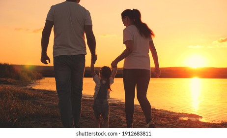 A small child holds the hand of mom and dad at the sunset sky. Childhood with parents at dawn. Happy family life. Mother, father and kid in the glare of the sun. Travel along the beach, near the coast