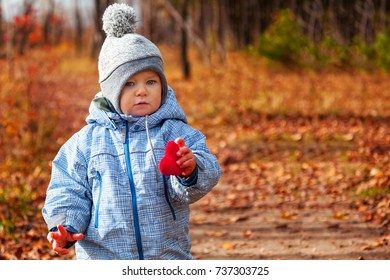 a small child holds a heart in his hand, walks through the autumn park