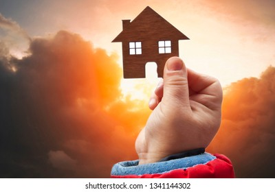 A small child holds a little wooden house in his hand in front of sunset in the sky