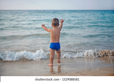 Small child  kid boy running to the sea lake ocean beach at evening sunset looking far away.  Happy lifestyle childhood concept. View from back.  Cyprus , Ayia-napa