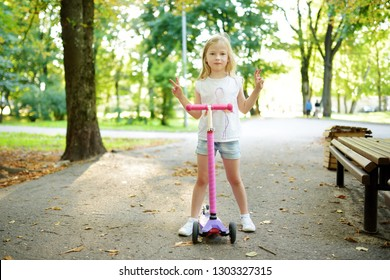 Small child learning to ride a scooter in a city park on sunny summer evening. Cute little girl riding a roller. Active leisure and outdoor sport for kids.