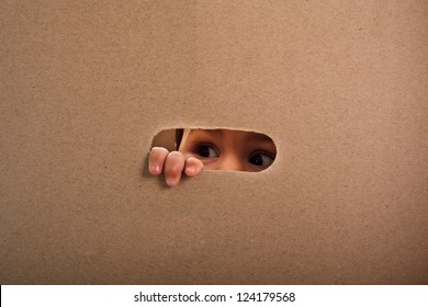 A small child looking out the gap of craft box