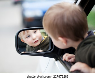 Small child looking to outside mirror