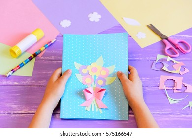 Small child made a greeting card with flowers for mom. Step. Child holds a card in his hands. Tools and materials for children's art creativity on table. Mother's day or March 8 greeting card DIY idea