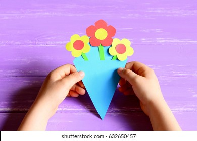 small child made paper flowers crafts for mothers day or birthday child holds and shows