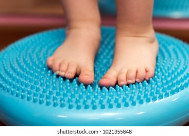 a small child massaging his feet while standing on the rug