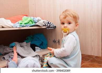 a small child near the closet with things
