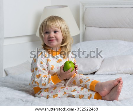 0a40957ea9 A small child in pajamas and barefoot with green Apple in hands. The kid in