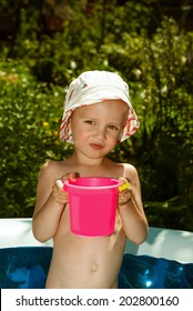 Small child in Panama in an inflatable pool with pink bucket of water.