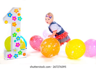 a small child playing in its first birthday with colorful balloons on a white background