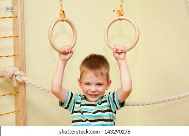 Small child playing sports at sport center. Kid exercising on gymnastic rings