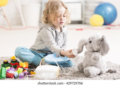 Small child playing with toy elephant, asthma treatment device lying on a floor