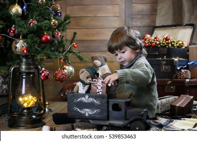 small child playing with toys in a room with christmas decorations