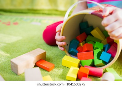 Small child playing with wooden blocks on green carpet - shallow depth of field