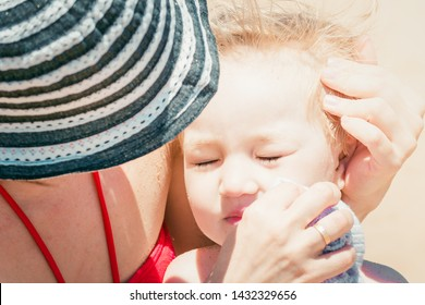 Small child pressed against his mother from sunstroke