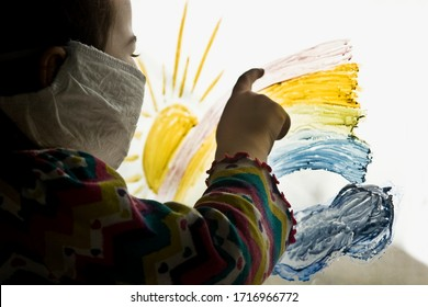 A small child in a protective mask looks out the window in quarantine. A child in a mask on his face looks through the painted rainbow on the glass to the street during self-isolation during quarantin