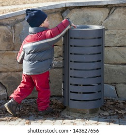 Small child putting a waste or litter in a street rubbish can or bin.