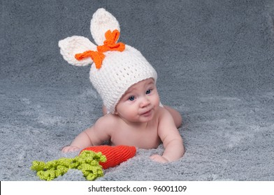 A small child with a rabbit ears. Lying on his stomach with a carrot.