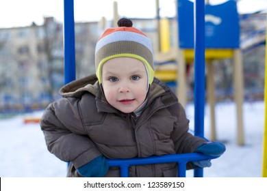 Small child riding on swing in winter
