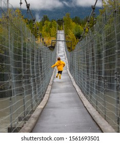 Small child running fast across a suspension bridge his feet are not touching the ground.