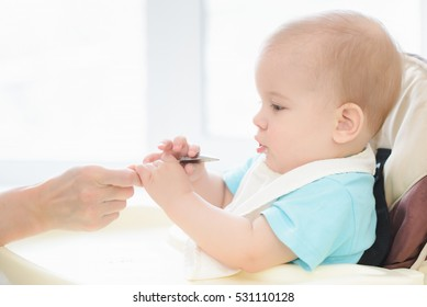 small child sits on a chair and eating with spoon