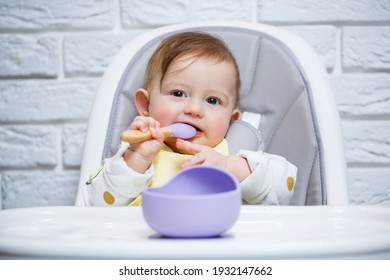 A small child sits on a highchair and eats food from a plate with a spoon. Baby silicone utensils for feeding babies