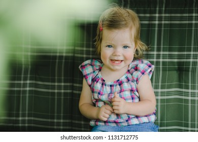 The small child sits on the sofa in room
