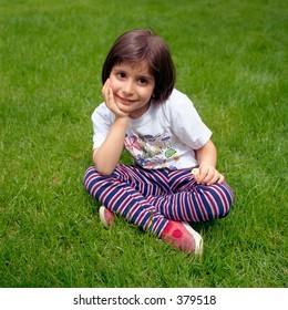 Small Child sitting on grass lawn and smiling
