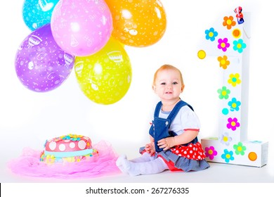 a small child sitting on a white background isolated in his birthday among balloons near the cake