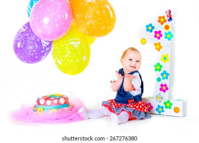 a small child sitting on a white background isolated in his birthday among balloons