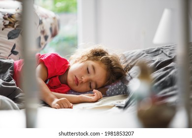 A small child sleeps sweetly in his bed. Healthy sleep of the girl, ventilation. Morning, wake up, sunlight from the window. Early ascent to kindergarten, school.