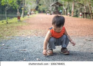small child squat on a trail ground in a natural park picking up stone and looking down to the ground
