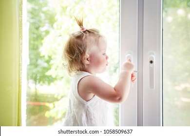 small child is standing on windowsill and opens window. Locks on windows prevent children from falling out of window. Girl playing with window handle