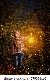 small child standing in the snow holding a candle lit lantern in the coastal forest.