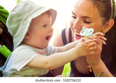 A small child in a stroller playing with Mother. Young Mother playing with toddler.