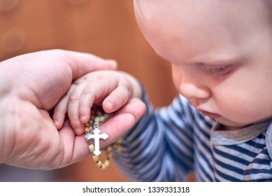 A small child takes a rosary from his dad's hand