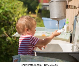 Small child, toddler, 2 years old, blonde, in striped T-shirt washes his hands under washstand outdoors in countryside