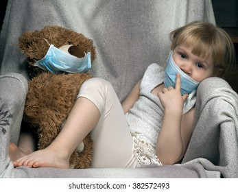 Small child with a toy bear cub in a medical mask. The girl is sad. Concept - an allergy to dust, wool, asthma. risk of infection, the viruses.