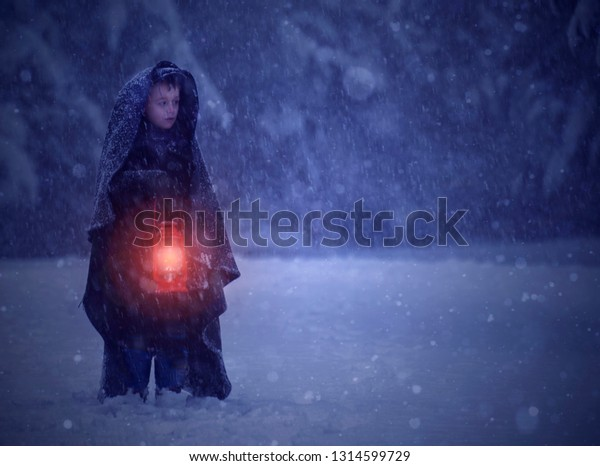 Small child walking in a winter storm wrapped in a blanket holding a retro candle lit lantern.