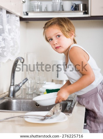 Small child washing dishes at domestic kitchen