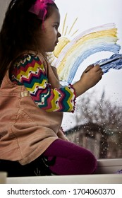 A small child at the window during quarantine paints a colorful rainbow in watercolor. The kid participates in the worldwide flash mob during quarantine - a rainbow pattern on a window pane.
