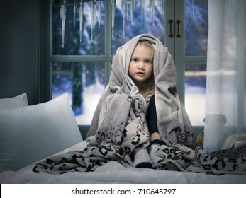small child wrapped in a blanket on the bed. Children's room window. Outside the window, snow, winter