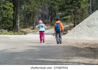Small children, brother and sister, walking together small road through a forest