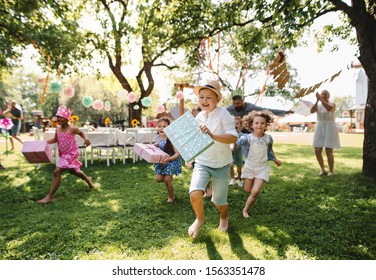 Small children ruunning with present outdoors in garden on birthday party.