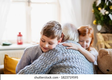 Small children with senior grandfather indoors at home at Christmas, hugging.